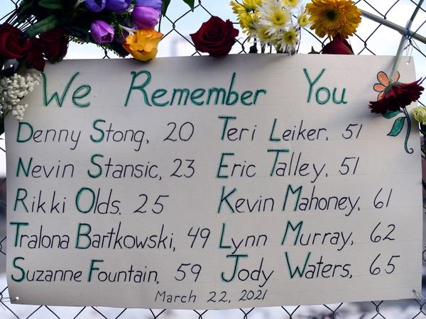 A sign framed with flowers lists victims' names on a fence outside a King Soopers grocery store in Boulder, Colo. The suspect in the mass shooting made his first court appearance on Thursday.