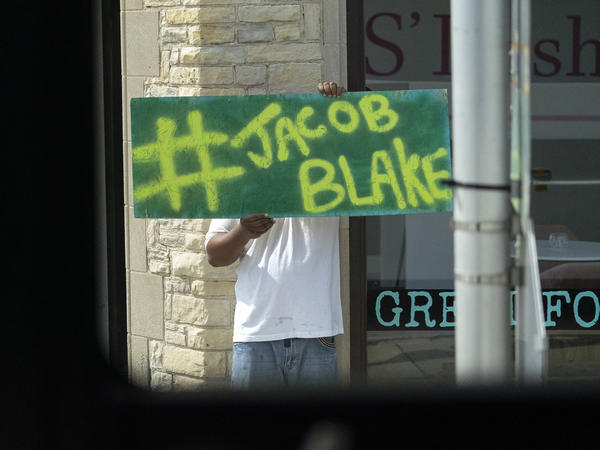 A Jacob Blake sign was on display as the motorcade of then-presidential candidate Joe Biden passed by in Kenosha Wis., on Sept. 3, 2020. A team of attorneys representing Blake have filed an excessive force lawsuit against the officer who shot and paralyzed him in August.