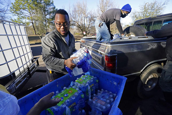 Madonna Manor maintenance supervisor Lamar Jackson left, stacks bottled water brought by Mac Epps of Mississippi Move, as part of the supply efforts by city councilman and State Rep. De'Keither Stamps to a senior residence in west Jackson, Miss. (Rogelio V. Solis/AP Photo)
