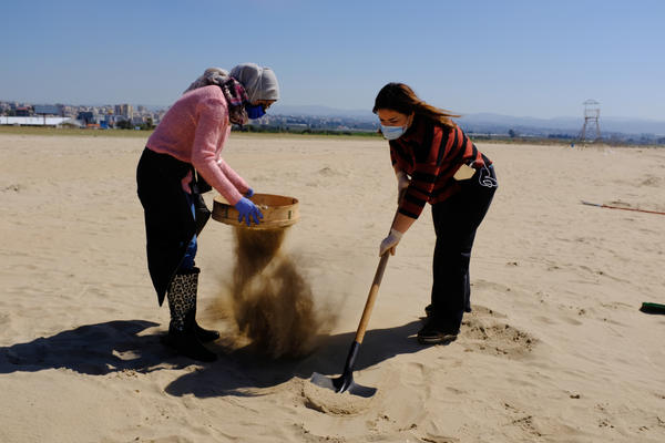 Marine biology student Ranim Tahhan, 21, pictured left, and another volunteer work to clean Tyre beach from the pollution caused by an oil spill in the eastern Mediterranean Sea.