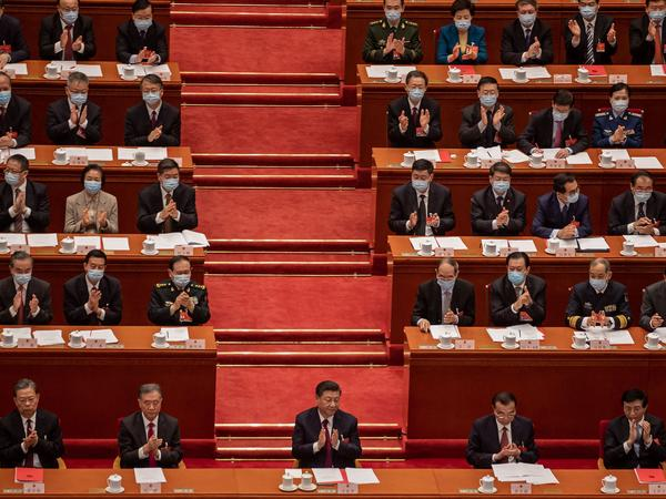 China's President Xi Jinping (C) applauds with other leaders and delegates after they voted on changes to Hong Kong's election system during the closing session of the National People's Congress at the Great Hall of the People in Beijing on March 11, 2021.