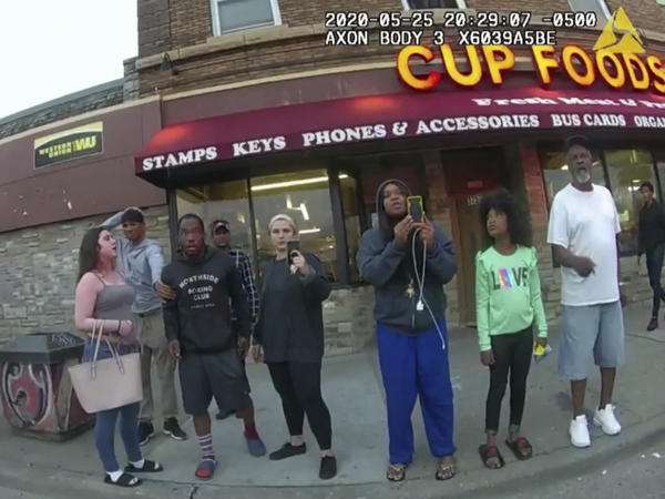 This image from a police body camera shows people gathering as former Minneapolis police officer Derek Chauvin was recorded pressing his knee on George Floyd's neck for several minutes as onlookers yelled at Chauvin to get off and Floyd said that he couldn't breathe on May 25, 2020 in Minneapolis.