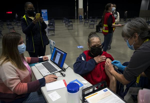 Susan Hughes receives a Covid-19 vaccine at the mass vaccination site on March 13, 2021 at Seattle's Lumen Field Event Center.
