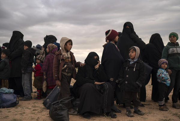 Women and children evacuated out of the last territory held by Islamic State militants wait to be screened by U.S.-backed Syrian Democratic Forces (SDF) in the desert outside Baghouz, Syria, on Feb. 27.