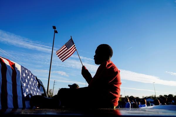 Xavier Watts, 9, waves an American flag during a campaign rally for Georgia Democratic U.S. Senate candidates Jon Ossoff and Raphael Warnock on Nov. 15 in Marietta, Ga.
