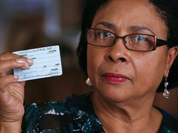Rena Logan, a member of a Cherokee Freedmen family, shows her identification card as a member of the Cherokee tribe at her home in Muskogee, Okla., in this photo from October 2011. She is among the some 8,500 people whose ancestors were enslaved by the Cherokee Nation in the 1800s.