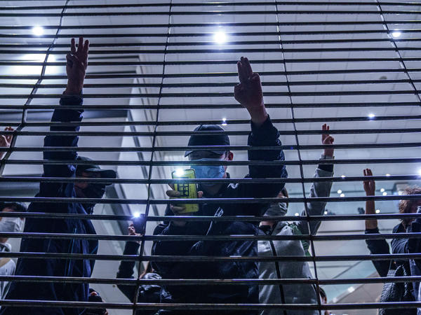 Pro-democracy demonstrators gesture with three-fingered salutes outside West Kowloon Magistrates Courts during a hearing for opposition activists charged with violating the city's national security law in Hong Kong Thursday, March 4, 2021. All 47 of the pro-democracy activists in a Hong Kong subversion case returned to custody Thursday after a marathon hearing ended with them being denied bail.