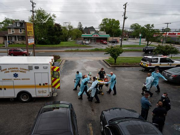 Firefighters and paramedics with the Anne Arundel County Fire Department in Maryland wear enhanced PPE, during the coronavirus pandemic, as they transport a patient after responding to a call for a cardiac arrest as a result of a drug overdose on May 6, 2020.