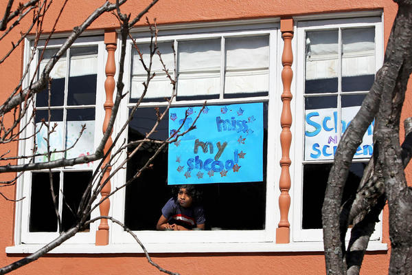 """Jeevan Guha, 6, offers a view of pandemic-era schooling with this homemade sign in San Francisco. The sign reads, """"I miss my school."""""""