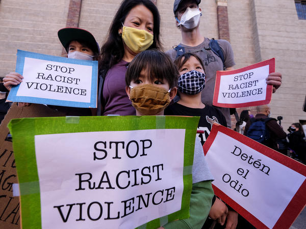 "A family wearing face masks and holding signs take part in a rally ""Love Our Communities: Build Collective Power"" to raise awareness of anti-Asian violence, at the Japanese American National Museum in Little Tokyo in Los Angeles, California, on March 13."