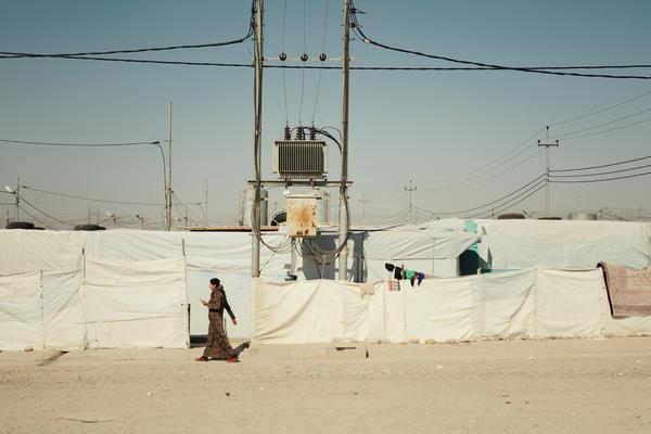 A Yazidi woman walks through the Khanke camp in northern Iraq in February.