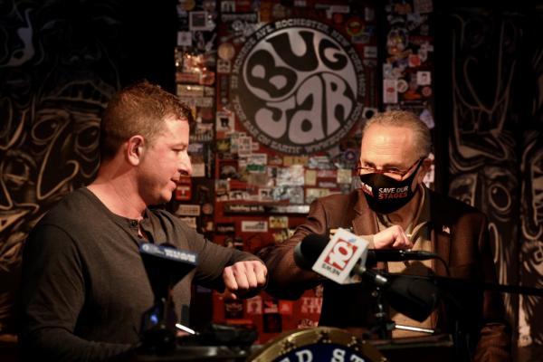 U.S. Senator Chuck Schumer and Bug Jar owner Aaron Gibalski elbow bump at press event