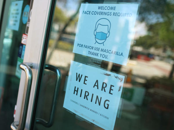 "A store in Miami displays a ""We are hiring"" sign on March 5. U.S. employers added 916,000 jobs in March, the biggest number since August, amid an improving pandemic outlook and trillions of dollars in stimulus passed by Congress."