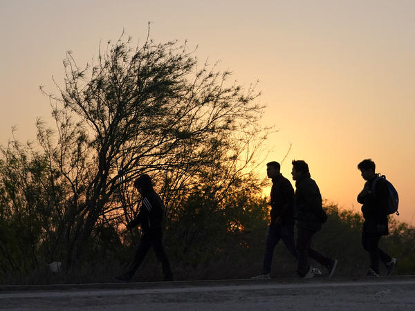 Migrants walk near a gate along the U.S. border with Mexico after being spotted by a U.S. Customs and Border Protection agent and taken into custody while trying to cross on March 21 in Abram-Perezville, Texas.