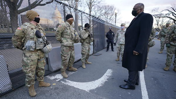 "Defense Secretary Lloyd Austin visits National Guard troops deployed at the U.S. Capitol on Jan. 29. The troops were deployed in the wake of the Jan. 6 Capitol attack. Under Austin's order, all military units are holding ""stand downs"" to discuss extremism in the ranks."