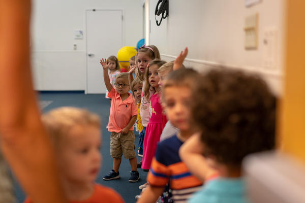 Children wait in line to grab their backpacks and find their classrooms during the first day of school at the Affton preschool center.