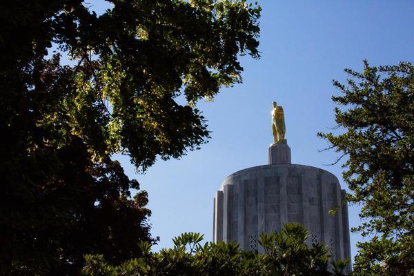 Sun glints off the pioneer atop the Oregon Capitol building in Salem, Ore., Saturday, June 29, 2019.