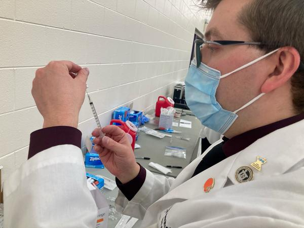 A technician from the Findlay College of Pharmacy fills a syringe with a dose of the Pfizer vaccine at a clinic in Reynoldsburg in February 2021.