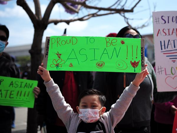 A boy holding a sign takes part in a Stop Asian Hate rally in Oakland, Calif.