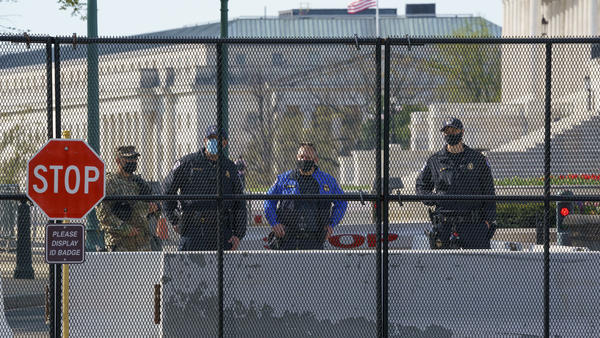 U.S. Capitol Police officers and members of the National Guard keep watch at the Constitution Avenue entrance to the East Plaza of the Capitol where an officer was killed when a man rammed a car into the barricade on April 2. The debate about whether there should be permanent fencing will be front and center when lawmakers return next week.