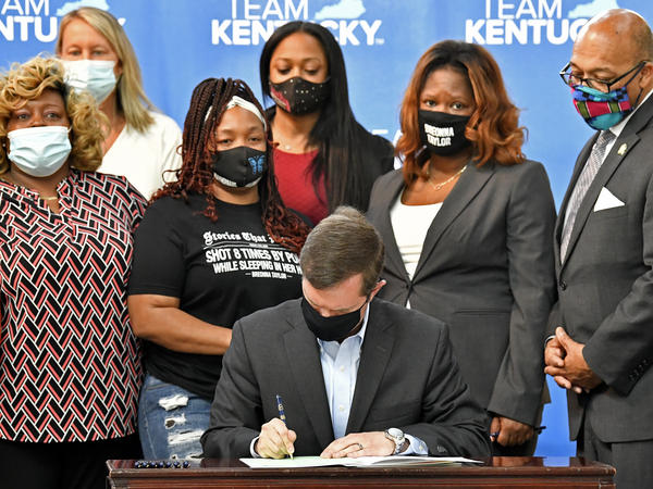 Kentucky Gov. Andy Beshear signs a bill on Friday limiting the use of no-knock warrants statewide. The governor was surrounded by members of Breonna Taylor's family including her mother, Tamika Palmer (standing behind Beshear at left).