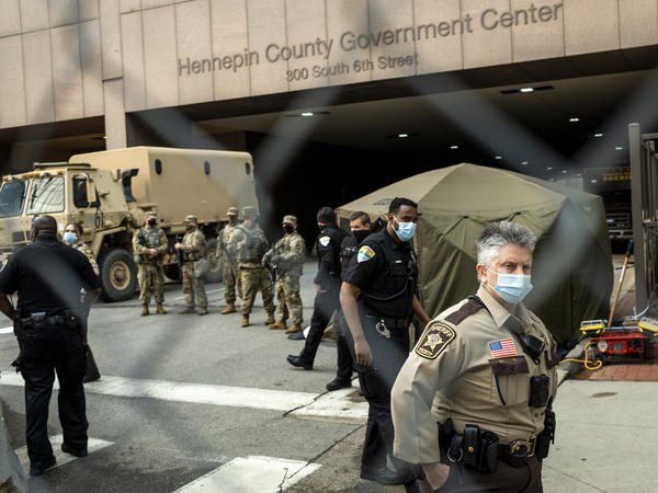 Jurors are escorted into the Hennepin County Government Center by sheriff's deputies. Here, members of the Minnesota National Guard and other agencies stand watch outside the building in Minneapolis.