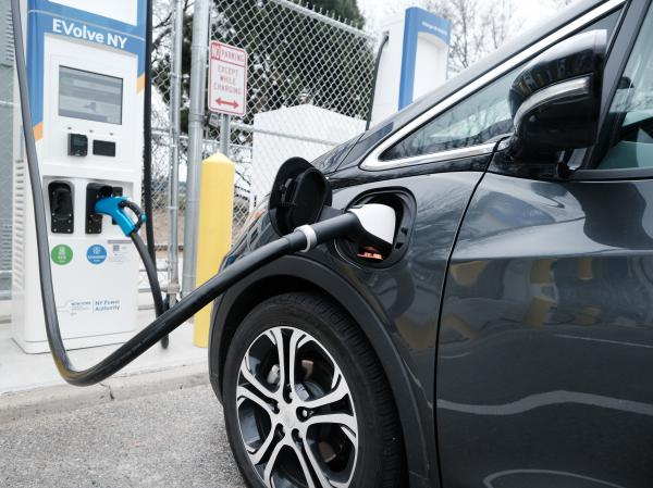 A driver uses a fast-charging station for electric vehicles at New York's John F. Kennedy Airport on April 2. As part of President Biden's $2 trillion infrastructure plan, $174 billion would go to supporting the production of electric vehicles in the U.S.