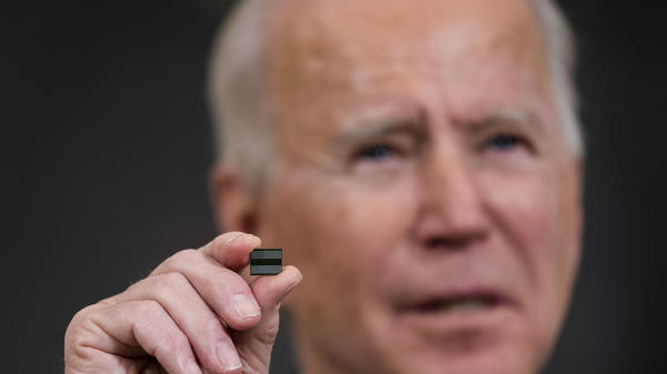 President Biden holds a semiconductor during remarks before signing an executive order on the economy at the White House on Feb. 24. On Monday, senior members of his team met with leaders across various industries to discuss a shortage of semiconductors.