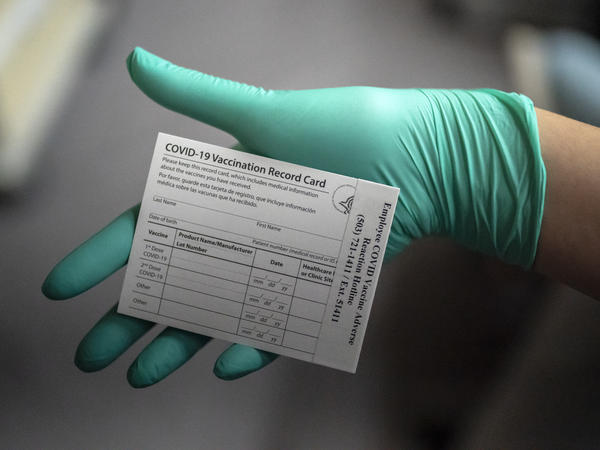 A healthcare worker displays a COVID-19 vaccine record card at the Portland Veterans Affairs Medical Center in December.