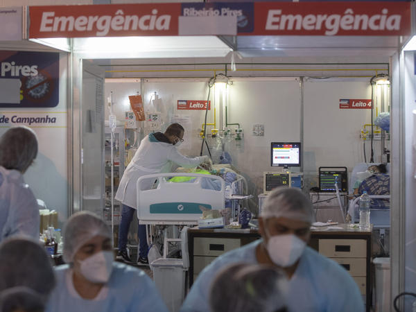 A health worker treats a COVID-19 patient at a field hospital in Ribeirao Pires, greater Sao Paulo area, on Tuesday.
