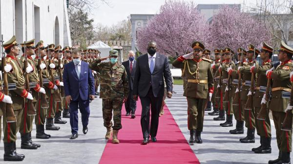 U.S. Defense Secretary Lloyd Austin, center, walks on the red carpet with Afghan officials as they review an honor guard at the presidential palace in Kabul, Afghanistan, on March 21. President Biden said the U.S. will withdraw all remaining troops from the country by Sept. 11, ending the U.S. involvement in the America's longest-ever war.