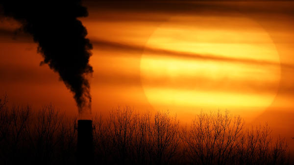Emissions from a coal-fired power plant are silhouetted against the setting sun in Independence, Mo., in February. President Biden is announcing a new pledge for the U.S. to reduce carbon emissions under the Paris climate agreement.