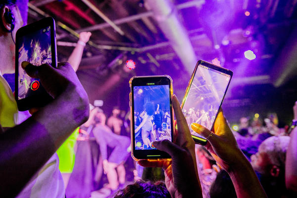 You can do a lot of things with minimal risk after being vaccinated. Although our public health expert says that maybe it's not quite time for a rave or other tightly packed events. Above: Fans take photographs of Megan Thee Stallion at a London show in 2019.