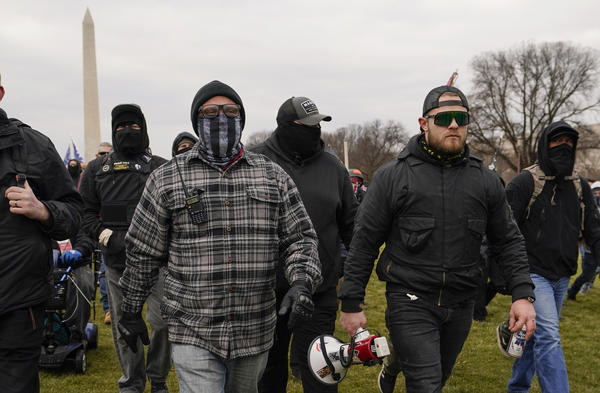 Proud Boy members Joseph Biggs (left) and Ethan Nordean, carrying a megaphone, walk toward the U.S. Capitol on Jan. 6. A federal judge ordered them detained pending trial given the conspiracy charges against them.