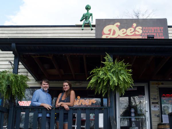 Daniel Walker and Amy Dee Richardson, owners of Dee's Country Cocktail Lounge pose with the alien on their roof, Rick.