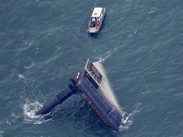 A rescue boat is seen next to the capsized lift boat Seacor Power seven miles off the coast of Louisiana in the Gulf of Mexico Sunday. The vessel capsized during a storm last Tuesday.