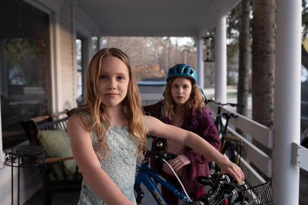 Azalea Morgan, 9, (left) and her sister Ember Morgan, 10 (right) stand with their bikes on the porch of their home in Andover, New Hampshire. The sisters biked to New York City from Andover with their mom to raise awareness about climate change in 2019.