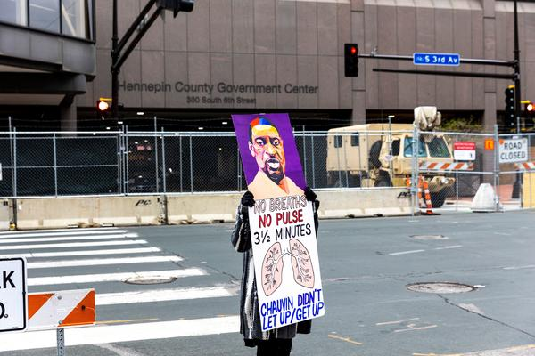 A lone protester stands outside the Hennepin County Courthouse on Monday as lawyers presented closing arguments in the murder trial of Derek Chauvin. The jury is now deliberating.