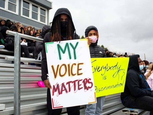 Students hold signs during a walkout at Tartan High School in Oakdale, Minn., where participants spoke, sang and did trauma-healing exercises together on the football field Monday.