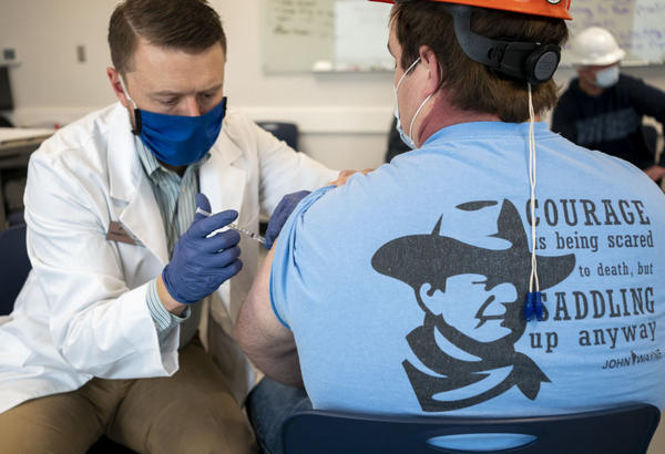 A pharmacist administers a dose of a COVID-19 vaccine to a worker at a processing plant in Arkansas City, Kan., on March 5. Researchers are concerned that vaccination rates in some rural communities may not keep up with urban rates.
