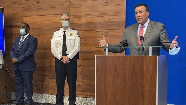Columbus, Ohio, Mayor Andrew Ginther speaks during a news conference Wednesday about the fatal police shooting of 16-year-old Ma'Khia Bryant on Tuesday. Columbus Public Safety Director Ned Pettus (left) and interim Police Chief Michael Woods listen.