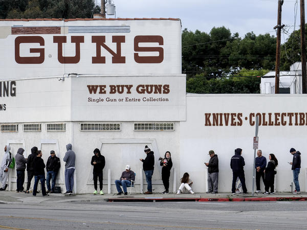 People wait in line to enter a gun store in Culver City, Calif., on March 15, 2020. The start of the coronavirus pandemic ignited a debate about whether businesses such as gun stores should be deemed essential and allowed to stay open. The start of the pandemic sparked a rise in gun sales, according to retailers and industry insiders.
