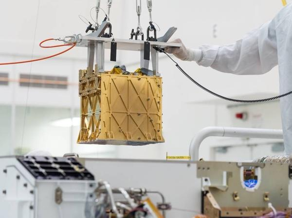 Technicians at NASA's Jet Propulsion Laboratory lower an instrument known as MOXIE, or the Mars Oxygen In-Situ Resource Utilization Experiment, into the belly of the Perseverance rover. NASA announced the instrument had produced oxygen from the Martian atmosphere.