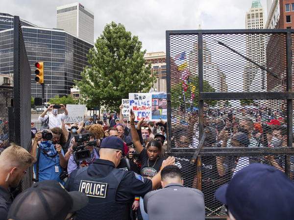 Protesters gather outside the entrance to a rally for then-President Donald Trump in June in Tulsa, Okla. A new state law increases penalties for protesters who block public roadways and grants legal immunity to drivers who unintentionally harm them as they try to flee.