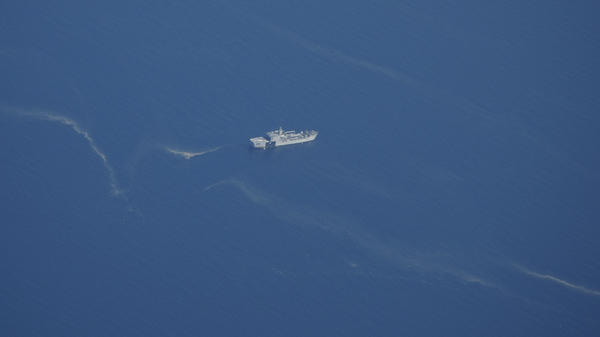 An Indonesian navy ship works near what appears to be oil slicks during a search Friday for the submarine KRI Nanggala 402 in the Bali Sea.