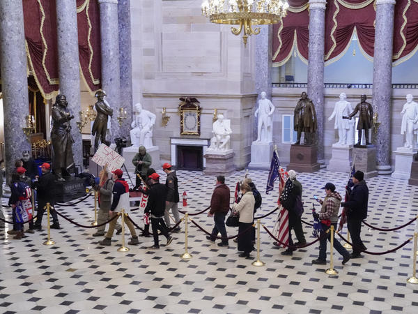 """Supporters of then-President Donald Trump walk through Statuary Hall of the U.S. Capitol on Jan. 6. A New York man was arrested Thursday after allegedly boasting on a dating app he had stormed the Capitol and """"made it all the way into Statuary Hall."""""""