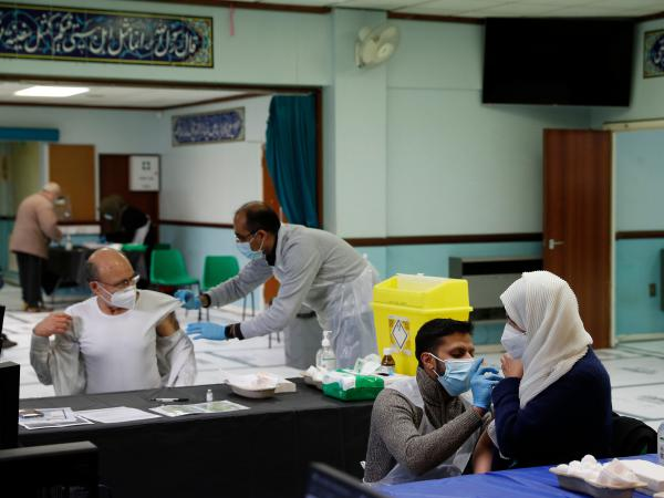 """People receive the AstraZeneca COVID-19 vaccine at the Al-Abbas Islamic Center, converted into a vaccination clinic in Birmingham, England, in January. Sheikh Nuru Mohammed, the imam at the mosque, recognized many of his congregants were hesitant to get the """"jab,"""" as it's called, due to false rumors and distrust of government. So he began to fight disinformation during his sermons."""