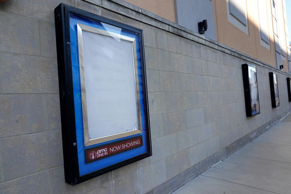 Empty frames that would normally hold movie posters hang on the front of an AMC theater shuttered by the coronavirus pandemic on Dec. 4, 2020, in Rosemont, Ill.