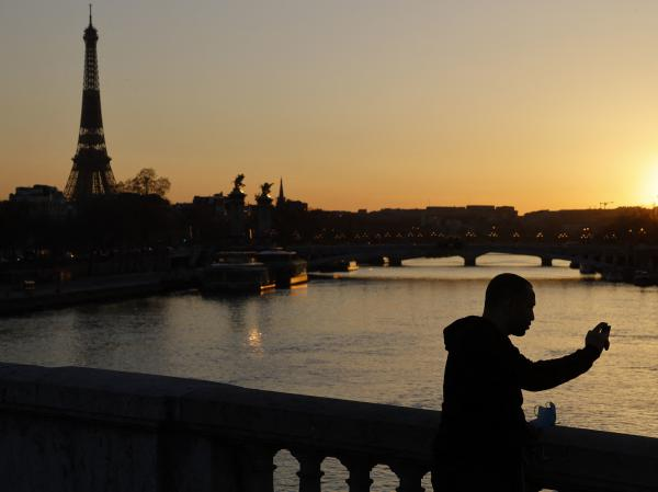 A man takes a picture at sunset with the Eiffel Tower in the background in March in Paris. The president of the European Commission says fully vaccinated Americans will be able to visit the European Union this summer.
