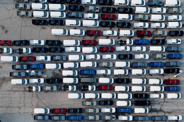 In this aerial photo, pickup trucks and vans are seen last month in a parking lot outside a General Motors assembly plant where they are produced in Wentzville, Mo. A key component in the car industry is in short supply: computer chips. Taiwan's chipmakers are racing to meet demand.